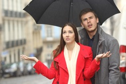 Portrait of a disgusted couple annoyed in a rainy day under the rain and an umbrella in winter