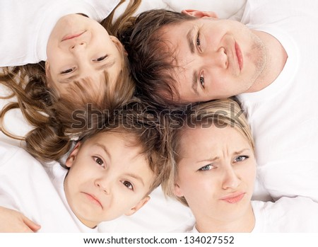 Portrait of a  displeased family having fun together lying on a bed at home - top view