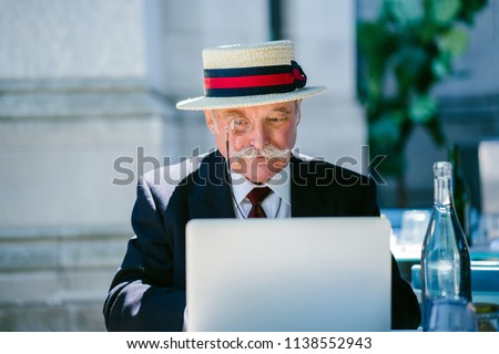 Portrait of a distinguished elderly Caucasian (European, British) gentleman working on his laptop computer during the day at a cafe. He is wearing a suit and tie, monocle and hat and has a moustache.