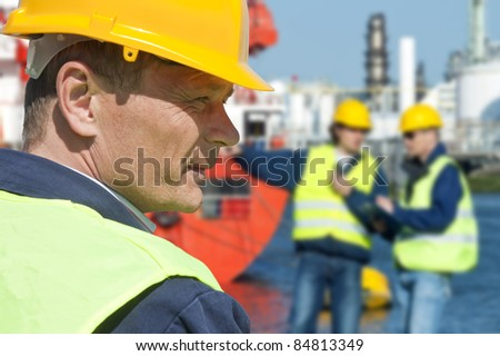 Portrait of a docker in front of a harbor scene with two of his coworkers out of focus in the background