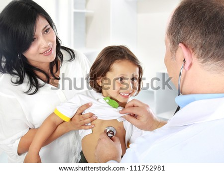 Portrait of a doctor examining heartbeat of the kid with stethoscope