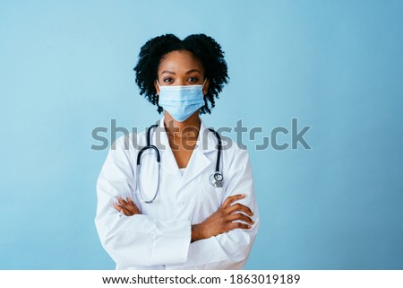 Portrait of a doctor in lab coat with face mask and arms crossed, isolated on blue background