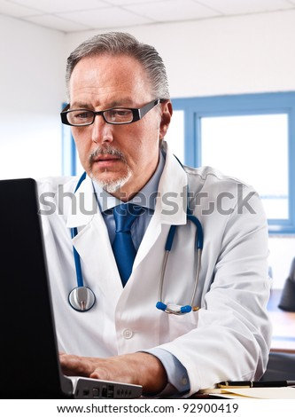 Portrait of a doctor using his laptop - stock photo
