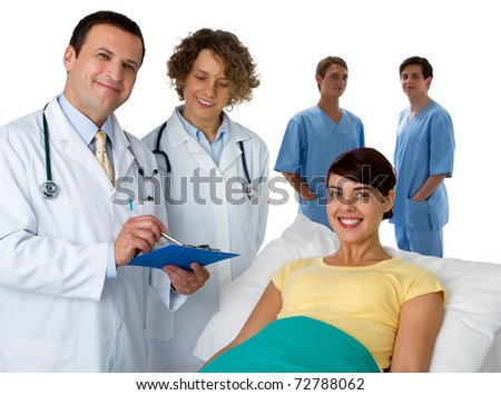 Portrait of a doctor with three of his co-workers with a patient