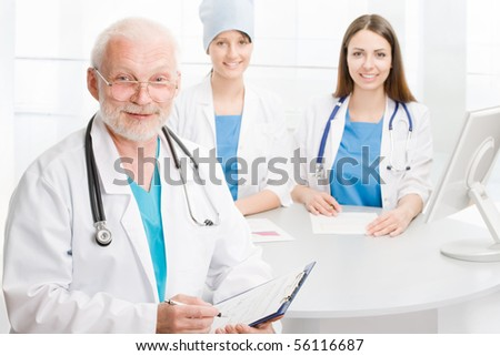 Portrait of a doctor with two co-workers sitting  in the background