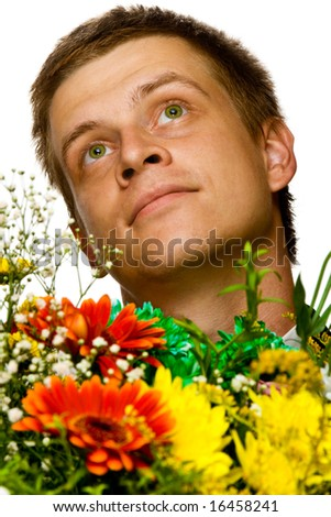 Portrait of a dreaming or enamored young man with flowers, isolated, on white background