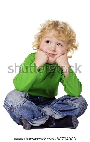 Portrait of a dreamy Boy sitting on a floor. Isolated over white