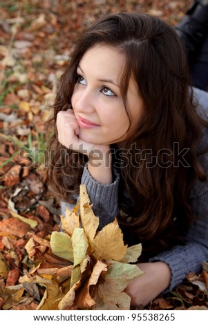 Portrait of a dreamy girl lying with leaves in the autumn park