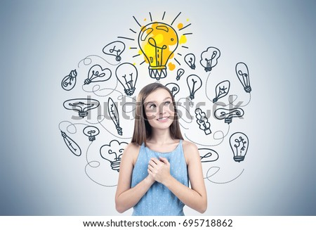 Portrait of a dreamy teen girl wearing a blue dress and holding her hands near the hart. She is standing near a concrete wall with a bright yellow light bulb above her and many other bulbs around her.