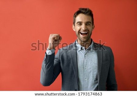 Portrait of a ecstatic young businessman cheering while standing in front of a red background Foto stock ©