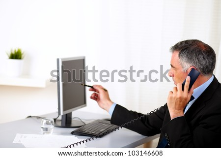 Portrait of a elegant businessman pointing the computer screen at the office