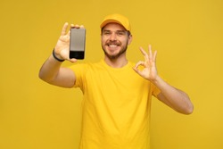 Portrait of a excited happy young delivery man in yellow cap standing isolated over white background. Looking camera showing display of mobile phone.