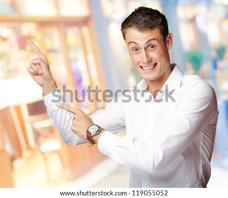 Portrait Of A  Excited Young Man Pointing Up, Indoor