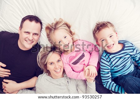 Portrait of a family lying on a bed in their pajamas.