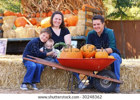 Portrait of a family of four at a pumpkin patch in autumn