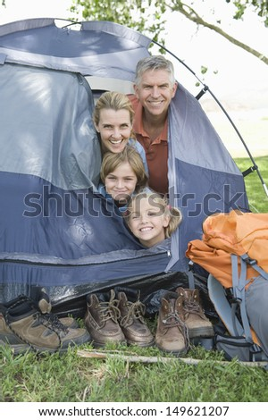 Portrait of a family of four smiling from a tent