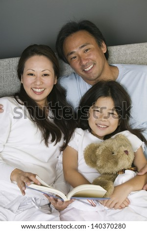 Portrait of a family reading in bed together at home