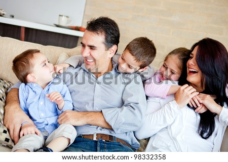 Portrait of a family sitting inside the house and smiling