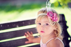 portrait of a fashion baby girl with flower headband close up outdoor