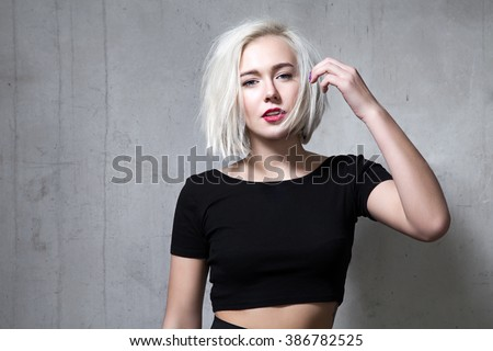 Portrait of a fashion blonde with short hair and wearing a black T-shirt on the background of a cement wall