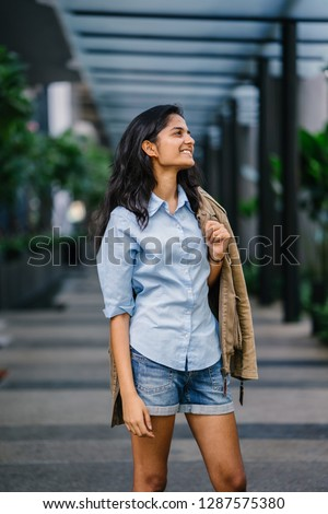 Portrait of a fashionable and casual Indian Asian woman in a shirt and shorts with a brown jacket draped over her shoulder in the city. She is smiling confidently and playfully.  #1287575380
