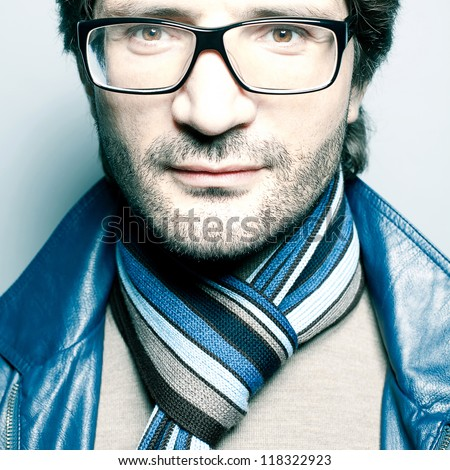 Portrait of a fashionable handsome man in blue jacket with striped scarf over light blue background. Close-up. studio shot