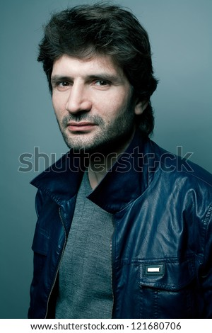 Portrait of a fashionable handsome man in gray sweater (pullover) and blue leather jacket over blue (green) background. studio shot
