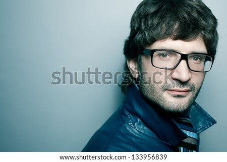 Portrait of a fashionable handsome mature man in blue jacket with striped scarf posing over light blue background. Close-up. Copy-space. Studio shot