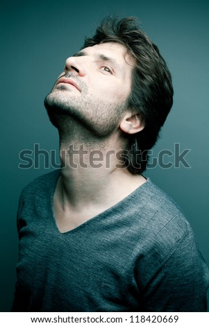 Portrait of a fashionable handsome model in gray sweater (pullover) over blue (green) background with his chin up. Close-up. studio shot
