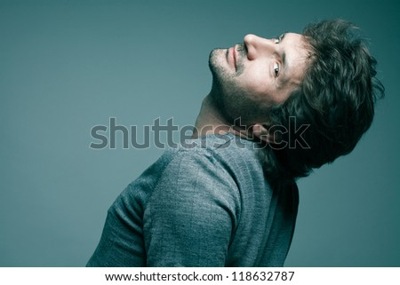 Portrait of a fashionable handsome model in gray sweater (pullover) over blue (green) background with his chin up. Studio shot