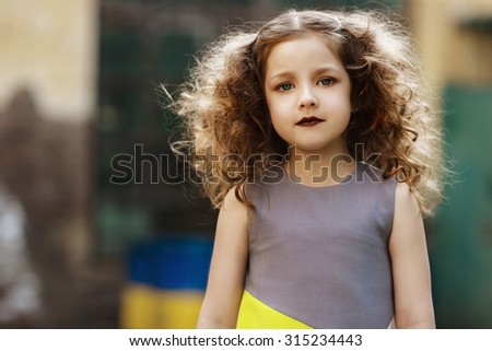 portrait of a Fashionable little girl with brown hair on the background of factory landscape