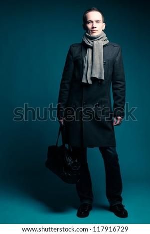 Portrait of a fashionable male model over dark blue background. studio shot
