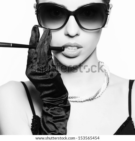 Portrait of a fashionable model in vintage sunglasses with a cigarette holder. Perfect skin. Great pearl accessories. Retro style. Close up. Black & white (monochrome) studio shot - stock photo