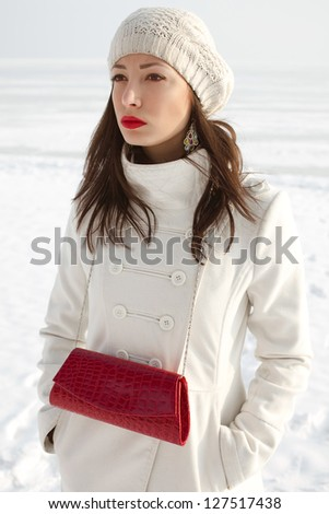 Portrait of a fashionable model in white coat and beret holding red leather clutch and posing at the winter seaside. Sunny weather. French style. Hands in the pockets. Outdoor shot.