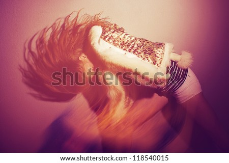 Portrait of a fashionable model with her long ginger hair up over purple background. studio shot with mixed light