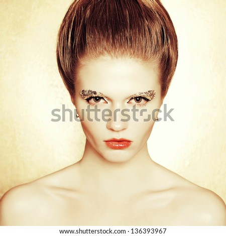 Portrait of a fashionable model with retro hairdo and arty make-up of golden foil posing over golden background. Vintage style. Perfect skin and hair. Studio shot