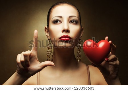 "Portrait of a fashionable model with sexy red lips holding red heart (love symbol) and showing ""L"" (love symbol) with her hand over golden background. Close up. Studio shot"