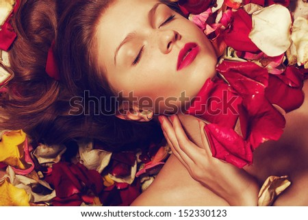 Portrait of a fashionable red-haired (ginger) model with sexy pink lips lying on fading rose petals background. Close up. Copy-space. Studio shot