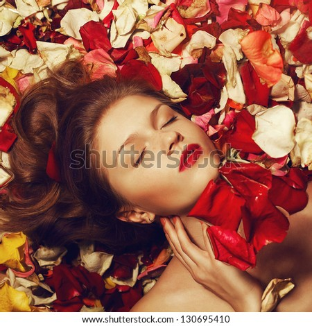 Portrait of a fashionable red-haired (ginger) model with sexy red lips lying on fading rose petals background. Studio shot