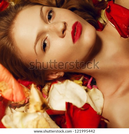 Portrait of a fashionable red-haired (ginger) model with sexy red lips lying on rose petals background. Studio shot