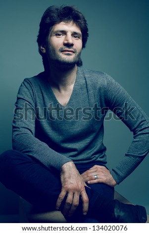 Portrait of a fashionable smiling handsome man in gray sweater (pullover) and blue jeans sitting and posing over dark blue (green) background. Studio shot