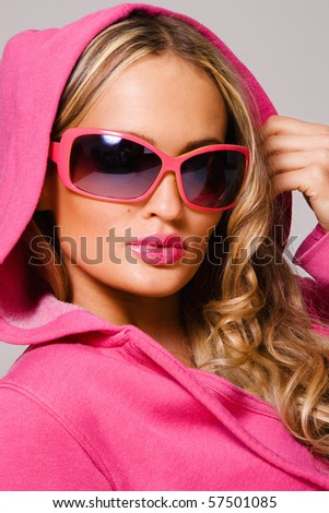 Stock Photo Portrait of a fashionable woman in pink cowl and sunglasses