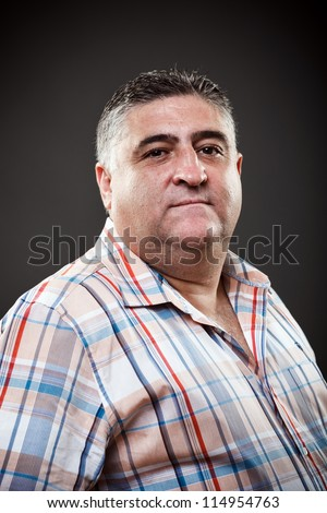 Portrait of a fat man posing in studio on gray background
