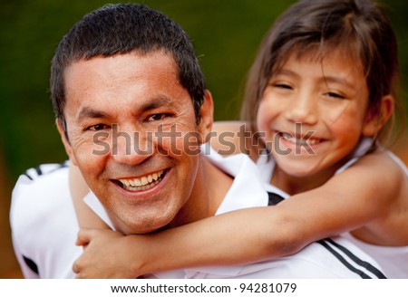 Portrait of a father and daughter at the tennis court smiling