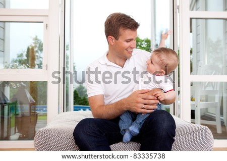 Portrait of a father and son smiling, looking at each other in a home interior