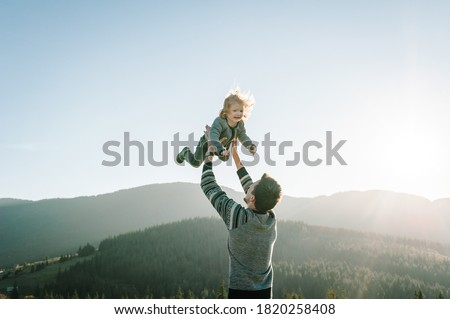 Portrait of a father holds, throws up happy daughter on hands walking on nature in autumn day. Dad and child playing in the mountains. Concept of family spending time together on vacation.