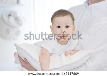 Portrait of a father with his lovely baby boy on white pillow