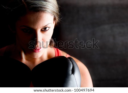 Portrait of a female boxer looking aggressive with her gloves
