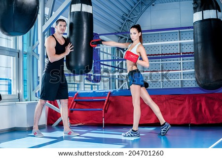 Portrait of a female boxer. Woman beats hand sports coach and holds a pear sports equipment