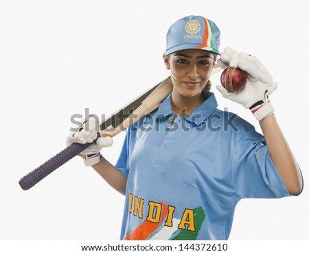 Portrait of a female cricketer holding a cricket bat and a ball